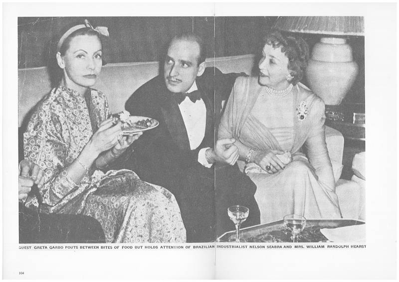 Guest Greta Garbo pouts between bites of food but holds attention of Brazilian industrialist Nelson Seabra and Mrs. William Randolph Hearst